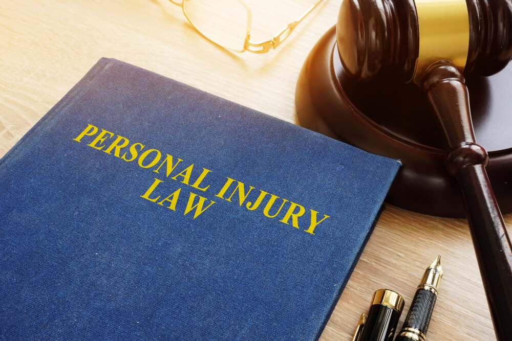 Blue personal injury law book with gavel in background